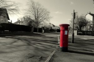 red mailbox on black and white uk street