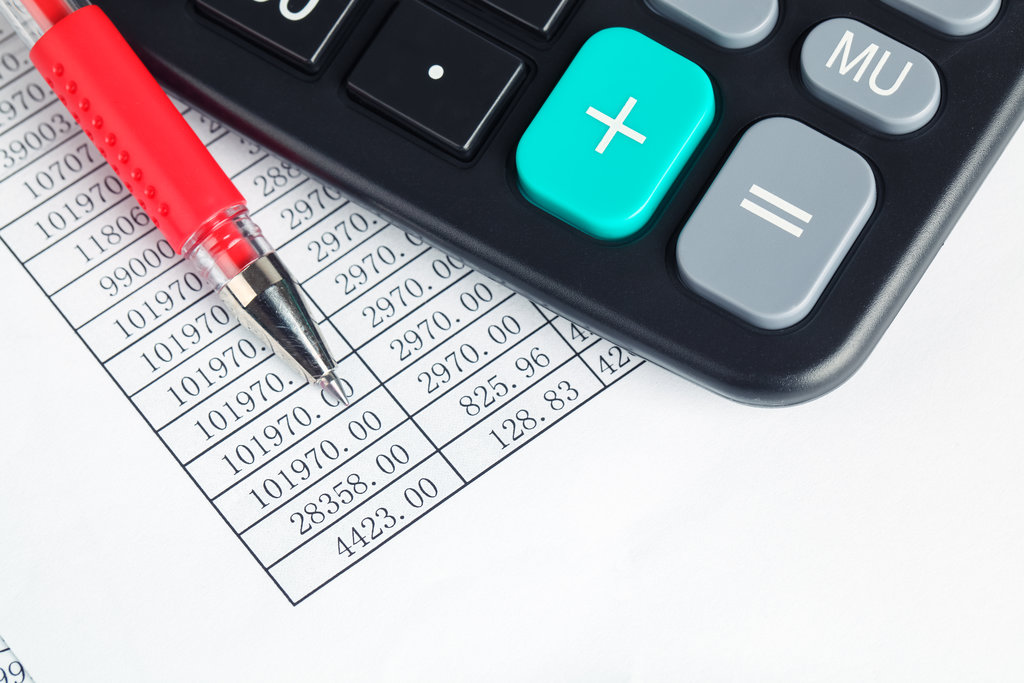 calculator and red pen on a digital report ,financial check concept