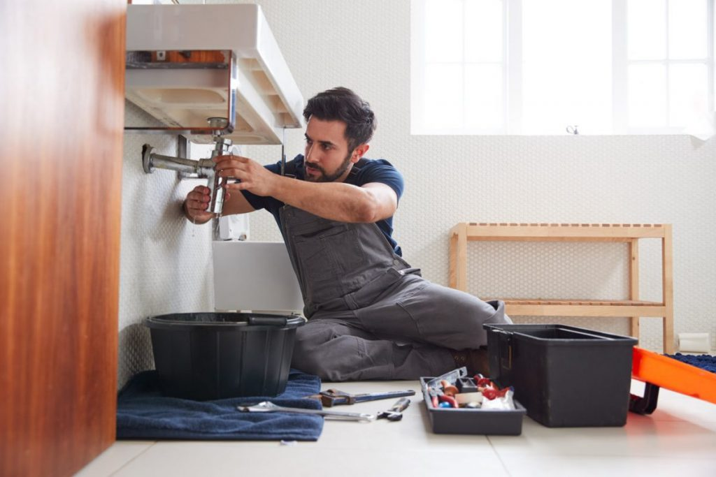 male plumber working in a home under the sink with tools