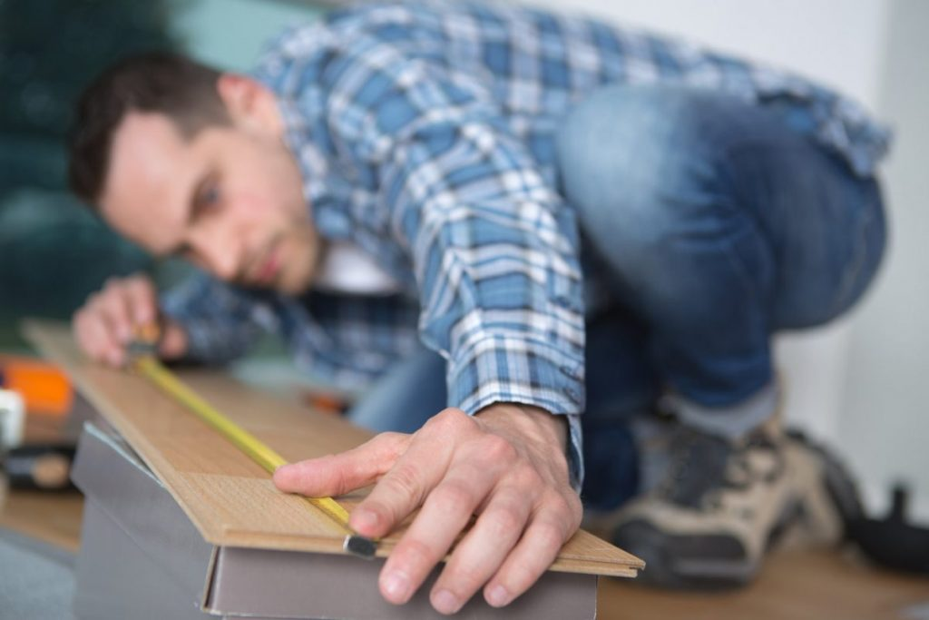 male carpenter undertaking measuring up work in clients home