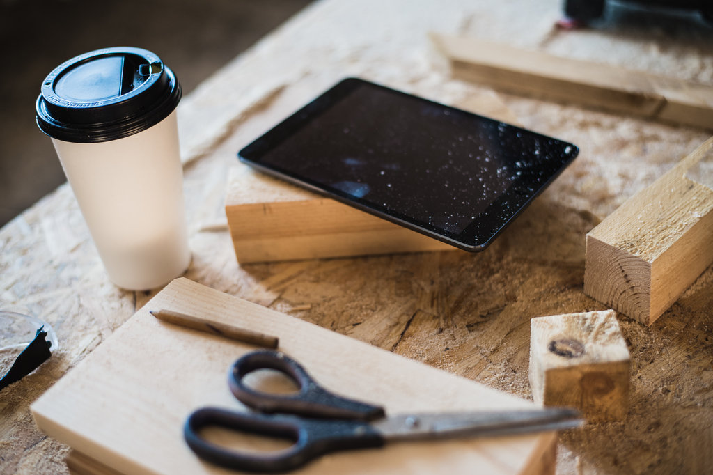Modern carpentry work place with tablet, coffee and scissors on table, in workshop.