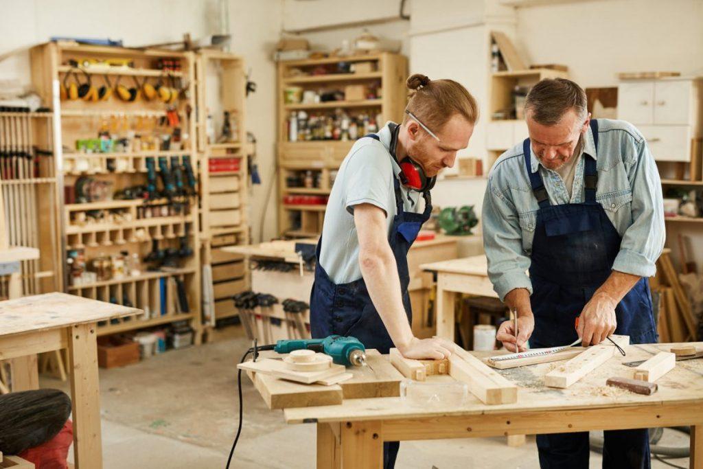 carpenter teaching apprentice his craft