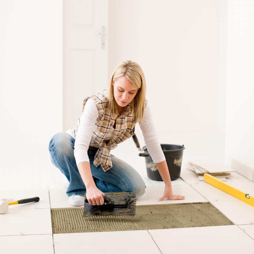 handywoman working on grouting tiles