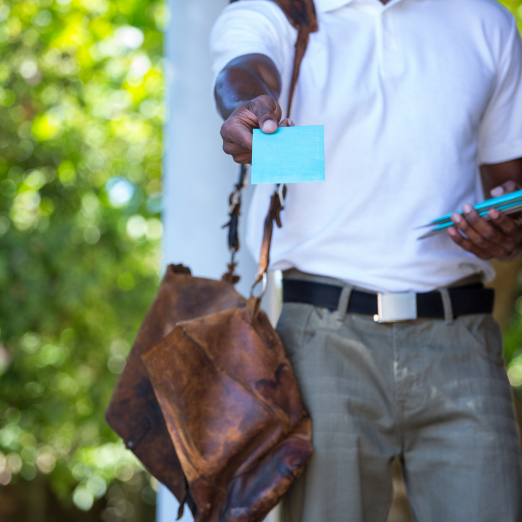 man with satchel handing out a blue business card