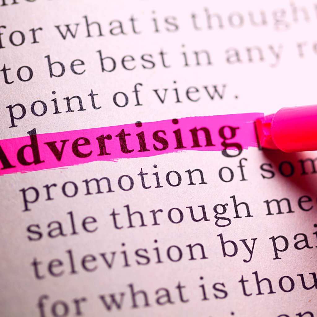 advertising highlighted in a newspaper with a pink highlighter