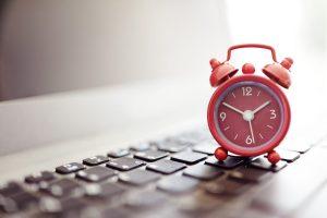 alarm clock sat on laptop time concept digital marketing